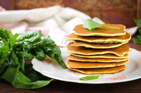 Vegetarian gluten free Spinach pancakes on wooden background