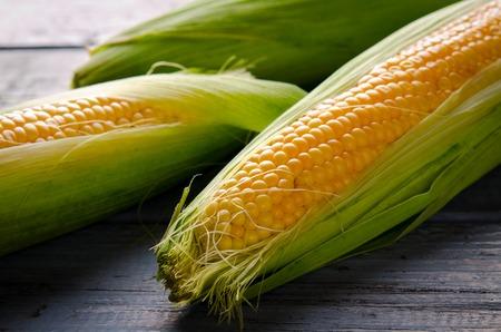 Raw organic yellow sweet corn on wooden background Stock fotó