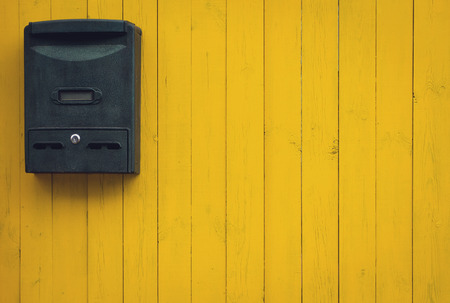 Old mailbox on a yellow wooden background, rustic style Stockfoto