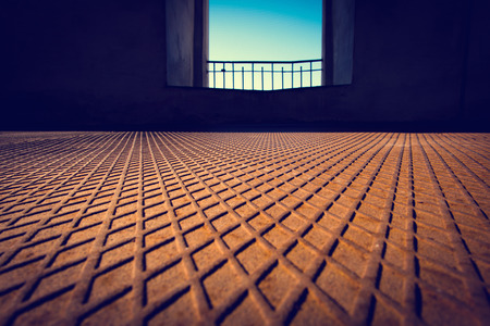 diamondplate: Rusted metal floor with a diamond-shaped pattern and a window in the background Stock Photo
