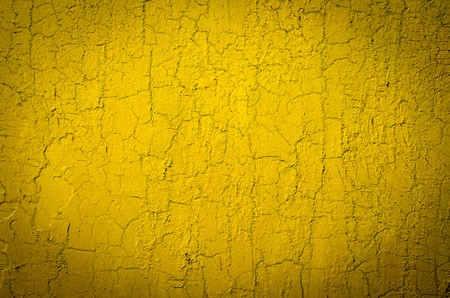 Wall painted in yellow, cracked. Abstract background Banco de Imagens