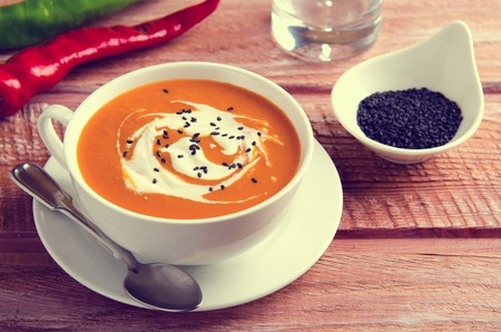 black sesame: Pumpkin Soup with tomatoes, chili, yogurt and black sesame seeds on wooden background