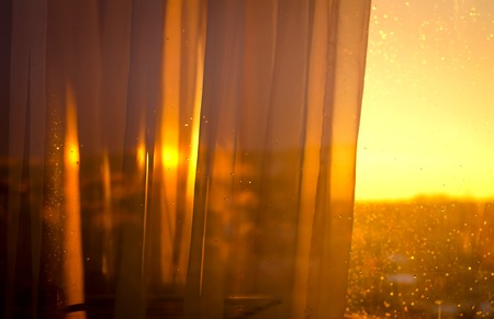 ocean of houses: View the sunset from balcony through curtains. Abstract background Stock Photo