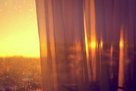 ventana abierta interior: Ver la puesta de sol desde el balcón a través de las cortinas. Resumen de antecedentes