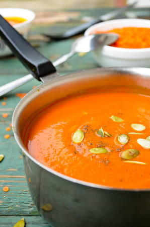puree: Vegetarian pumpkin-lentils cream soup with pepo seed on wooden background
