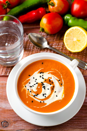 eating pastry: Pumpkin Soup with tomatoes, chili, yogurt and black sesame seeds on wooden background