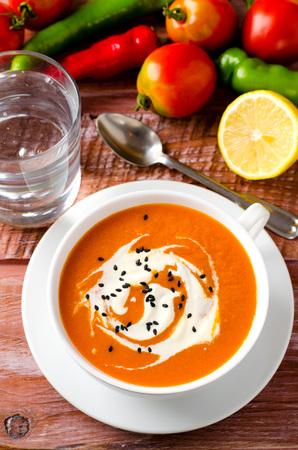 comida: Sopa de calabaza con los tomates, el chile, el yogur y semillas de s�samo negro sobre fondo de madera