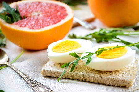 naranja color: Healthy breakfast with eggs, grapefruit and fresh arugula leaves on wooden background