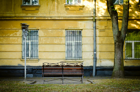 yellow house: bench near old yellow house facade with street lamp