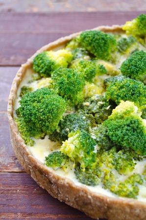 pasteleria francesa: Quiche casera con brócoli y queso sobre fondo de madera Foto de archivo