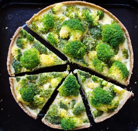 pasteleria francesa: Homemade quiche with broccoli and cheese on wooden background