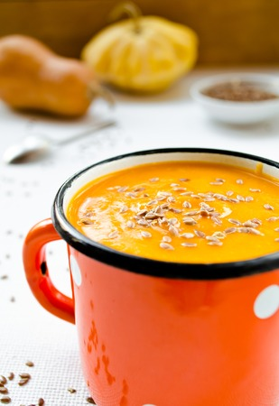 flax seeds: Vegetarian carrot-pumpkin cream soup with flax seeds in red cup