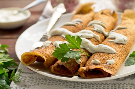 art style: Pancake rolls with mushrooms, yogurt dip and parsley on rustic background