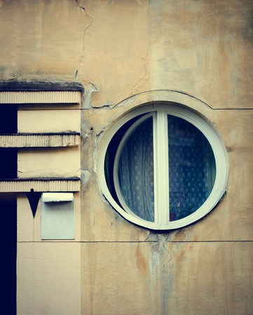 windows frame: Old circle windows frame on cement cracked wall. Vintage facade.