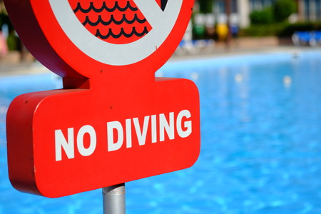 no diving sign: Red no diving warning sign at the poolside. Selective focus