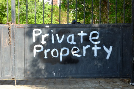 warning notice: Private Property notice on a barred gate, warning text.
