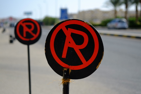 no parking sign: Red and black no parking sign on the road. Stock Photo