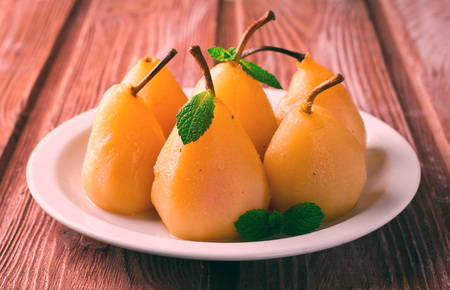 poach: Poached pears with mint on white plate, wooden background Stock Photo