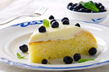 selective focus: Homemade cake with cream, blueberries and mint on white background, selective focus