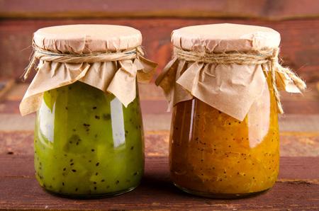 Pumpkin-Orange-Ginger-Poppy seed and Kiwi-Mint homemade jam on wooden background.