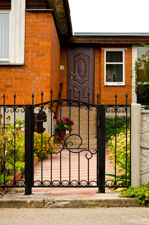 Red house facade with iron fence, green trees and flowers. Stock Photo