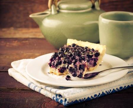 pie de limon: Bilberry, blueberry tart with lavender on white plate, wooden background, vintage style, toned