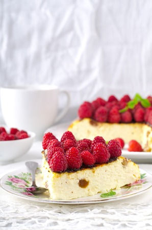 Cheesecake, souffle, cream mousse, pudding dessert with fresh raspberries and mint leaves on a white plate. Stock Photo