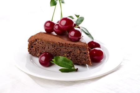 Chocolate cake with cherries and ganache cream on white background