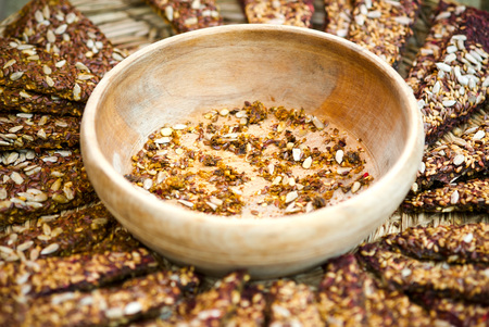 Slices or healthy, raw cereal crispy breads with nuts, seeds and spices on wooden board, selective focus