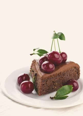 Chocolate cake with cherries and ganache cream on white background, toned Stock Photo