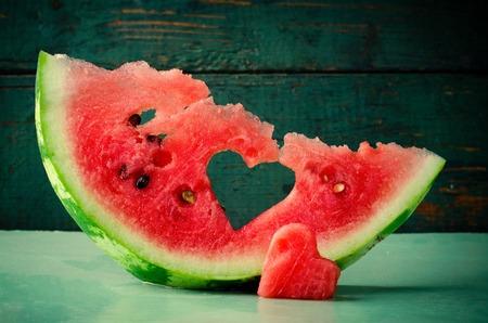 corazón sandía fresca jugosa en el fondo de madera de color turquesa. San Valentín, tarjeta de felicitación del amor Foto de archivo