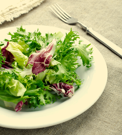 Green salad with spinach, frisee, arugula, radicchio, feta cheese and black sesame seed on blue wooden background Standard-Bild