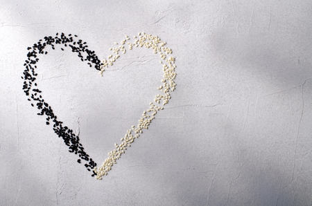 antipode: Heart made with black and white sesame seeds, on gray background. Love, Valentines day concept. Top view, copy space.