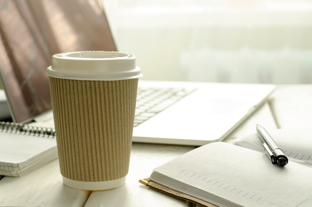 Paper cup of coffee on work-table with office stuff, notepad, laptop, pen and coffee cup Stock Photo