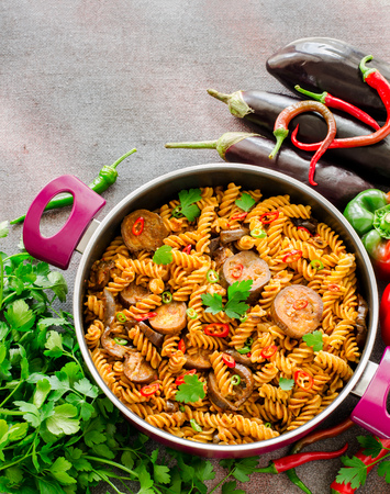 Attractive Mediterranean Eggplant Pasta In Pot With Tomatoes, Red Pepper And Parsley  On Grey Background.