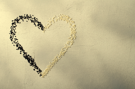 Heart made with black and white sesame seeds, on gray background. Love, Valentines day concept. Top view, copy space.