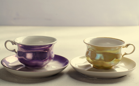 Empty colorful porcelain tableware. Yellow and violet cups on lilac background. Toned