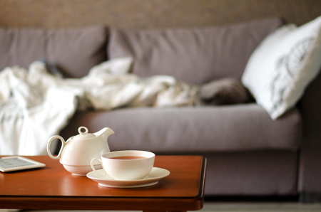 Cozy home interior with teapot, cup of tea and eBook Stock Photo