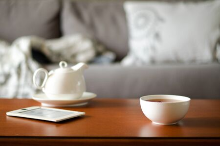 Cozy home interior with teapot, cup of tea and eBook. Horizontal, copy space Stock Photo