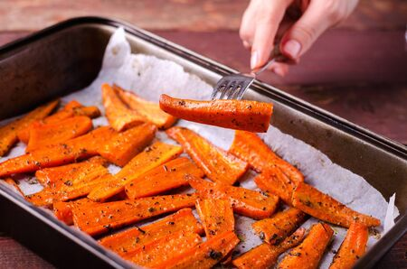 PIece of Roasted Caramelized organic Carrots with spices on fork in hand, horizontal