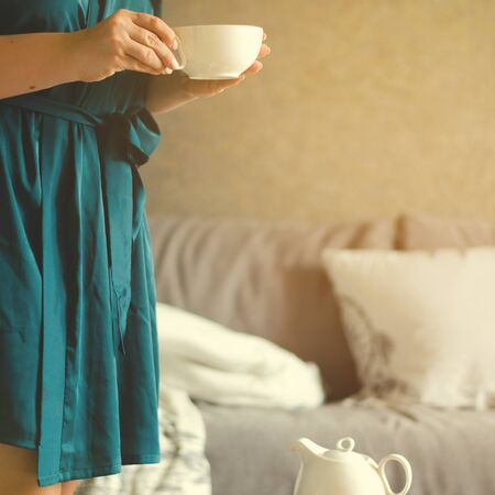 Cozy home interior with teapot and woman holding cup of tea.