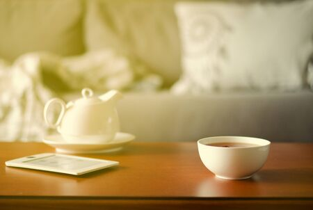 Cozy home interior with teapot, cup of tea and eBook Standard-Bild