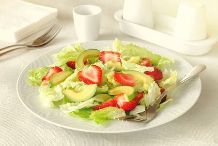 Salad with avocado, strawberries and lettuce on white background Standard-Bild