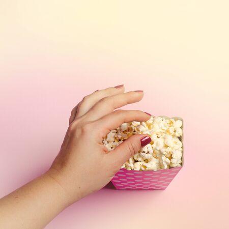 Paper box with popcorn on pink background Standard-Bild