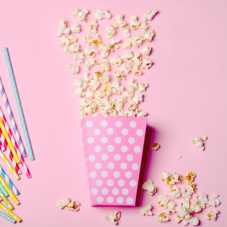 Paper box with popcorn on pink background