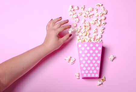 Paper box with popcorn on pink background with female hand. H