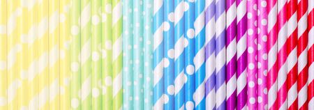 Colorful drink straws arrange in gradient, for background, top view. Banner, toned