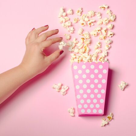 Paper box with popcorn on pink background with female hand. Sq