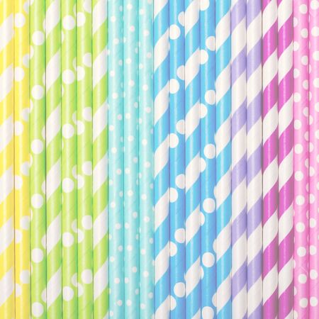 Colorful drink straws arrange in gradient, for background, top view. Square, toned
