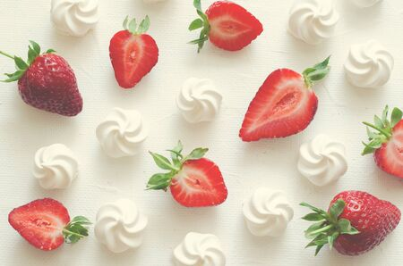 Pattern with strawberries and meringues on white background. Top view, toned
